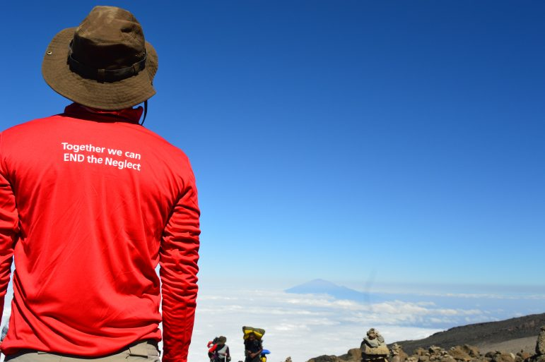 Man standing looking past the mountain with END Fund shirt