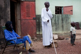 Moce is blind due to river blindness. He walks with a stick and a child to lead his way