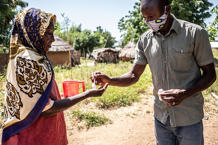 A Community Health Worker hands out treatments during a mass drug administration in Nigeria.