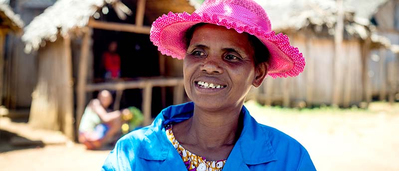 Smiling Bao, wearing a pink hat, looks off in the distance during a mass drug administration in Madagascar