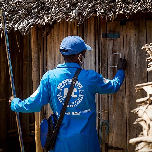A community health worker knocks on the door of a house during a mass drug administration in Madagascar