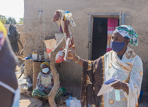 Minata Coulibaly speaks with a family in Mali about river blindness